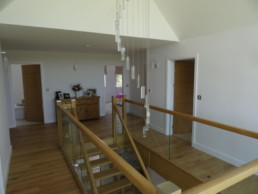 Stair Atrium of family home in York with feature chandalier and hardwood staircase with glass panels
