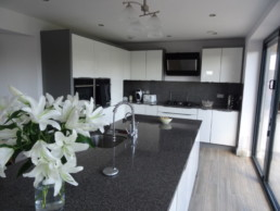 White and Grey Kitchen with granite workstops and 'Timber Plank' ceramic floor tiles to Modern Yorkshire Home